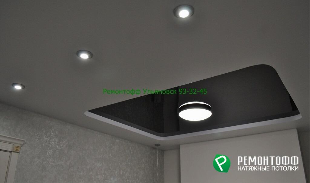 Двухуровневый натяжной потолок матовый белый и черный с тремя светильниками и одной люстрой.