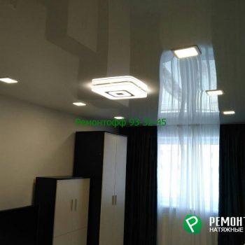 Глянцевый натяжной потолок белого цвета с люстрой и точечными светильниками в Ульяновске.
